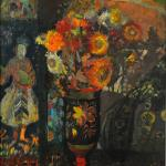 Still life of flowers in a vase, on a patterned table cloth in front of coloured prints.